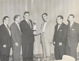 Larry receiving an award from Windsor Magic Circle president, Paul Desjardins. Ron Wilson is on the left. Circa—late 1950s.